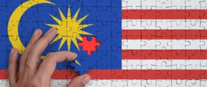 The Malaysian flag as a jigsaw puzzle, with a hand inserting a piece of a missing puzzle.